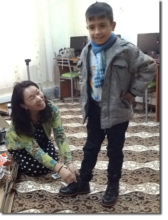 A refugee child receiving a new pair of shoes.